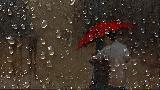 Immagine attraverso Abbraccio sotto ombrello attraverso finestrino bagnato
