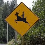Cartello stradale con cervo cavalcato da uomo