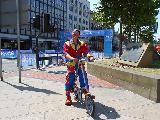 Ciclista in bicicletta divertente con vestiti sgargianti