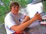 Giovane ragazzo in maglietta a tavola al lago in estate
