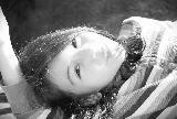 Immagine sorridente Ragazza dai tratti orientali sorridente sdraiata con mano sollevata